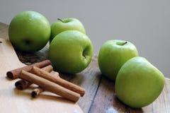 Nya gröna äpplen med kanelbruna pinnar Royaltyfri Bild