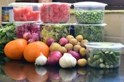 Nya gröna grönsaker i emballage och med löken, potatisar, vitlök och apelsiner, livsmedelsbutikshopping, dagliga behov Arkivbilder