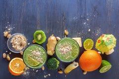 Nya gröna smoothies i ett exponeringsglas rånar med grönsaker, frukter och havreklor på en trätabell Arkivfoto