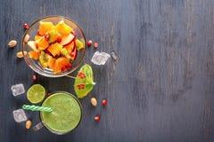 Nya gröna smoothies i ett exponeringsglas rånar och fruktsallad på en trätabell med is Arkivfoto