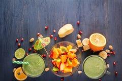 Nya gröna smoothies i exponeringsglas rånar frukter, grönsaker och fruktsallad på en trätabell Royaltyfria Foton