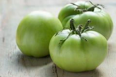 Nya gröna tomater på en träbakgrund Arkivfoton