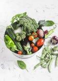 Nya grönsaker - broccoli, zucchini, beta, peppar, tomater, haricot vert, vitlök, basilika i en metallkorg på en ljus backgroun Royaltyfri Bild