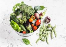 Nya grönsaker - broccoli, zucchini, beta, peppar, tomater, haricot vert, vitlök, basilika i en metallkorg på en ljus backgroun Royaltyfri Fotografi