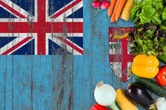 Nya grönsaker från Fiji på tabellen Laga mat begrepp p? tr?flaggabakgrund arkivbild