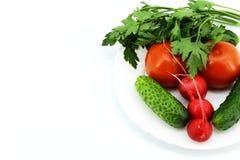 Nya grönsaker från trädgården på en vit rund platta arkivbild