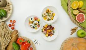 Nya grönsaker, frukt och sallader i plattorna på vit bakgrund, bästa sikt arkivfoto