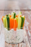 Nya grönsaker i en yoghurtsås i ett exponeringsglas arkivbild