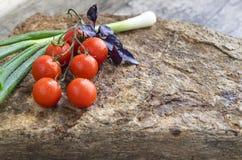 Nya grönsaker: körsbärsröda tomater, lök och basilika på en sten Royaltyfria Bilder