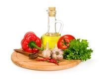 Nya grönsaker, kryddor och olivolja i en flaska Royaltyfri Bild