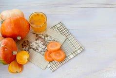 Nya grönsaker med pumpa och ett exponeringsglas av fruktsaft för havsbuckthorn royaltyfri fotografi