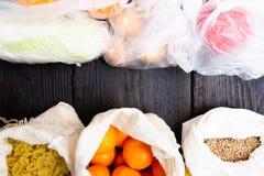 Nya grönsaker och frukter i ecobomullspåsar mot grönsaker i plastpåsar Nollförlorat begrepp - bruksplastpåsar eller mång- arkivfoton