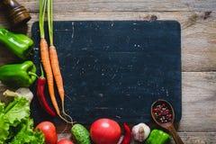 Nya grönsaker och kryddor för att laga mat på träskärbräda arkivbild