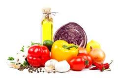 Nya grönsaker och olivolja på en vit bakgrund royaltyfria bilder