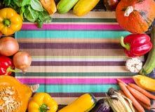 Nya grönsaker på en färgrik randig kökshandduk Höstbac Arkivfoton