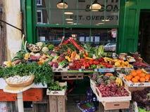 Nya grönsaker på en fruktställning i ett utomhus- lager i London många olika grönsaker och frukter royaltyfri foto