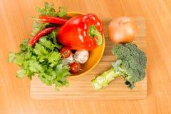 Nya grönsaker på en skärbräda Arkivbild
