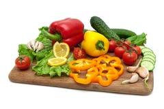 Nya grönsaker på en skärbräda på en vitbakgrund Arkivfoton