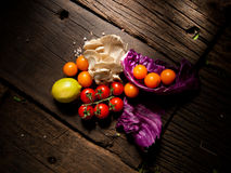 Nya grönsaker på en texturerad trätabell med dramatisk belysning Royaltyfria Bilder
