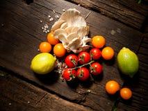 Nya grönsaker på en texturerad trätabell med solljus Överkanten metar ner Royaltyfri Fotografi
