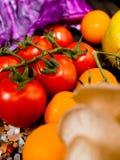 Nya grönsaker på en texturerad trätabell med solljus Tomater med örter och andra grönsaker Arkivbilder