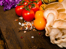 Nya grönsaker på en texturerad trätabell med solljus Tomater med örter, saltar och andra grönsaker Utrymme för titlar och tex Arkivbilder