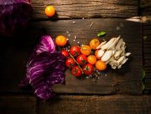Nya grönsaker på en texturerad trätabell med solljus Tomater och champinjoner med örter, saltar och andra grönsaker Arkivbilder