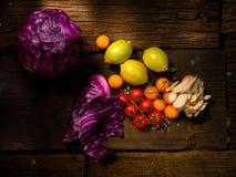 Nya grönsaker på en texturerad trätabell med solljus Tomater och champinjoner med örter, saltar och andra grönsaker Arkivbild