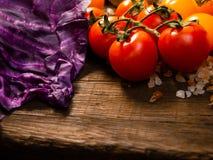 Nya grönsaker på en texturerad trätabell med solljus Tomater och röd kål med örter, saltar och andra grönsaker Royaltyfria Bilder