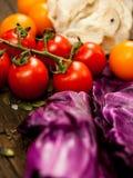 Nya grönsaker på en texturerad trätabell Närbildtomater Royaltyfri Foto