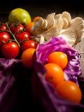 Nya grönsaker på en texturerad trätabell Närbildtomater och champinjon och röd kål Arkivfoton
