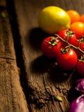 Nya grönsaker på en texturerad trätabell Närbildtomater och citron Royaltyfria Bilder