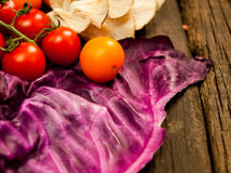 Nya grönsaker på en texturerad trätabell Närbildtomater och purpurfärgad kål Royaltyfria Foton