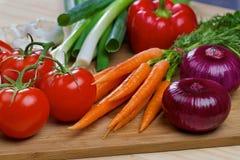 Nya grönsaker på ett träbräde Fotografering för Bildbyråer