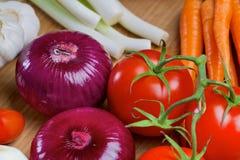 Nya grönsaker på ett träbräde Arkivbild