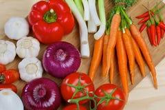 Nya grönsaker på ett träbräde Arkivbilder