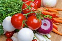 Nya grönsaker på ett träbräde Royaltyfria Bilder