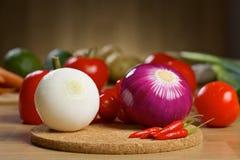Nya grönsaker på ett träbräde Arkivfoto