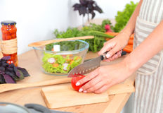 Nya grönsaker på skärbrädan faller i krukan, begrepp av matlagning Arkivbilder