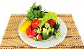 Nya grönsaker skivas utmärkt på uppläggningsfatet. Arkivfoto