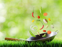 Nya grönsaker som in faller, wokar Arkivbild