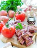 Nya grönsaker, tomater, vitlök, potatisar och persilja med rökte grisköttstöd Arkivbilder