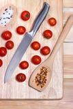 Nya grönsaker - tomatkörsbär och kniv på träbräde på tabellbakgrund Top beskådar sund begreppsmat Arkivbilder