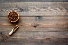 Nya grillade kaffebönor i bunke och skopa på mörk träcopyspace för bästa sikt för tabell klart bruk för bakgrundskaffe Arkivbilder