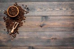 Nya grillade kaffebönor i bunke och skopa på mörk träcopyspace för bästa sikt för tabell klart bruk för bakgrundskaffe Arkivbild