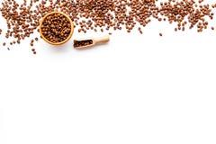 Nya grillade kaffebönor i bunke och skopa på vit copyspace för bästa sikt för tabell klart bruk för bakgrundskaffe Arkivfoto
