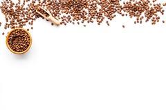 Nya grillade kaffebönor i bunke och skopa på vit copyspace för bästa sikt för tabell klart bruk för bakgrundskaffe Arkivbild