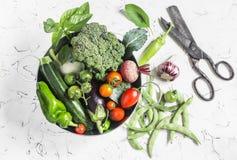 Nya grönsaker - broccoli, zucchini, beta, peppar, tomater, haricot vert, vitlök, basilika i en metallkorg på en ljus backgroun Arkivfoto