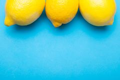 Nya gula citroner på den blåa tabellen, kopieringsutrymme royaltyfri fotografi
