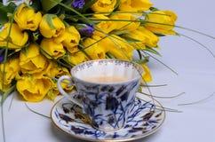 Nya gula tulpan och en kopp kaffe Arkivfoto